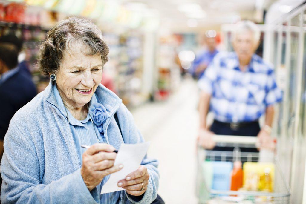 Smiling confident senior woman checks shopping list in supermarket
