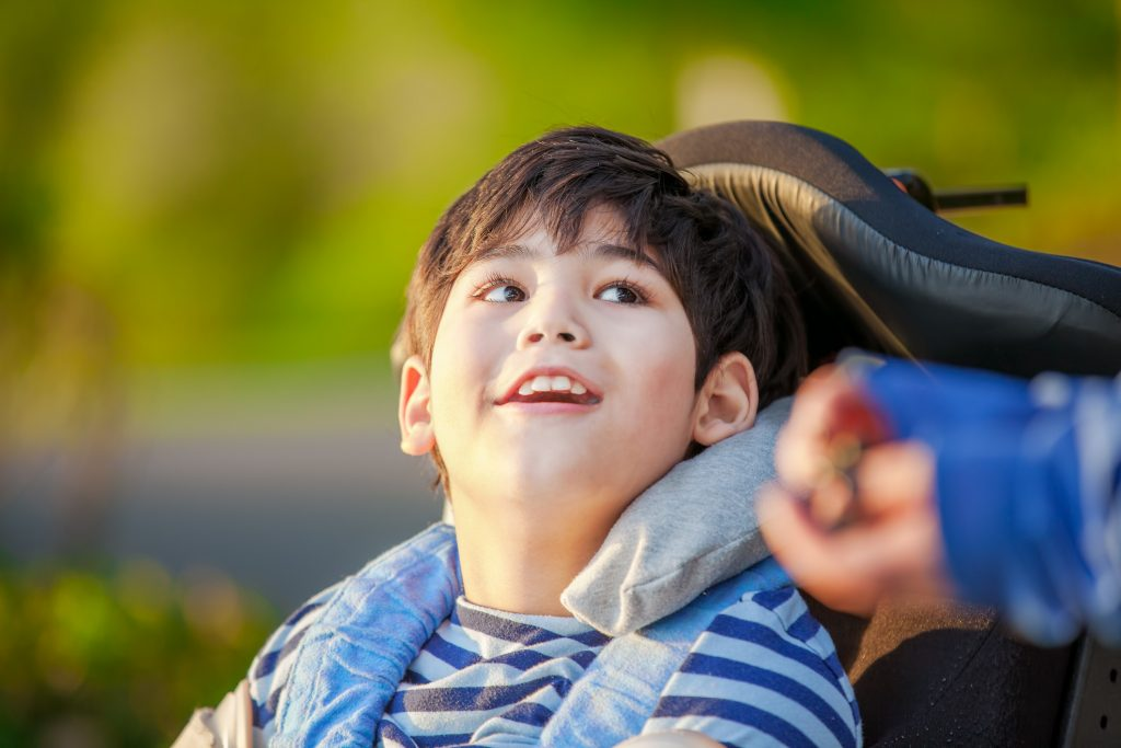 Young disabled boy in wheelchair looking up into sky