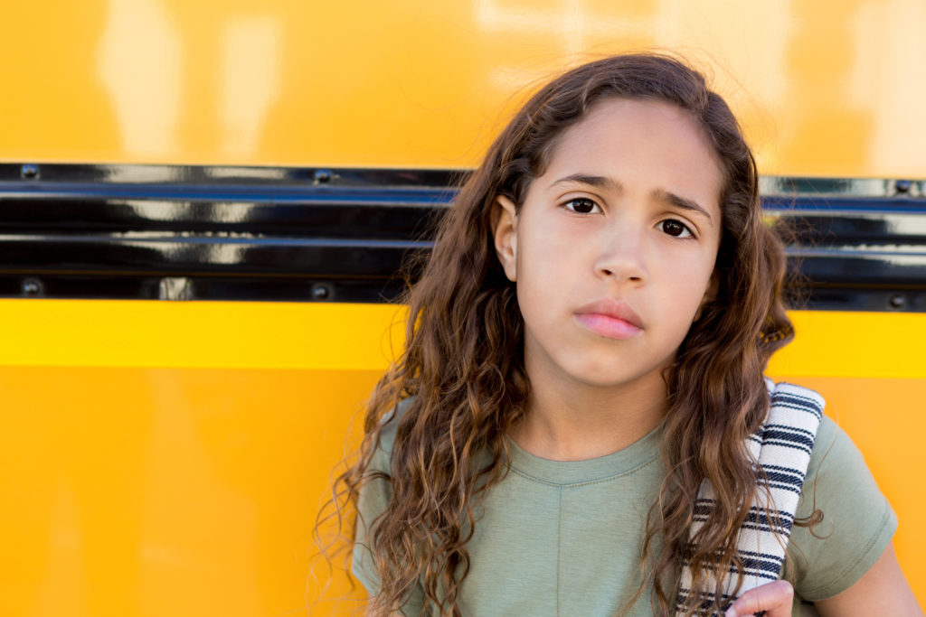 Young girl next to school bus