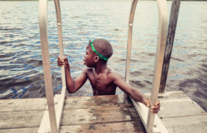 Young african-american boy with goggles swimming in lake.