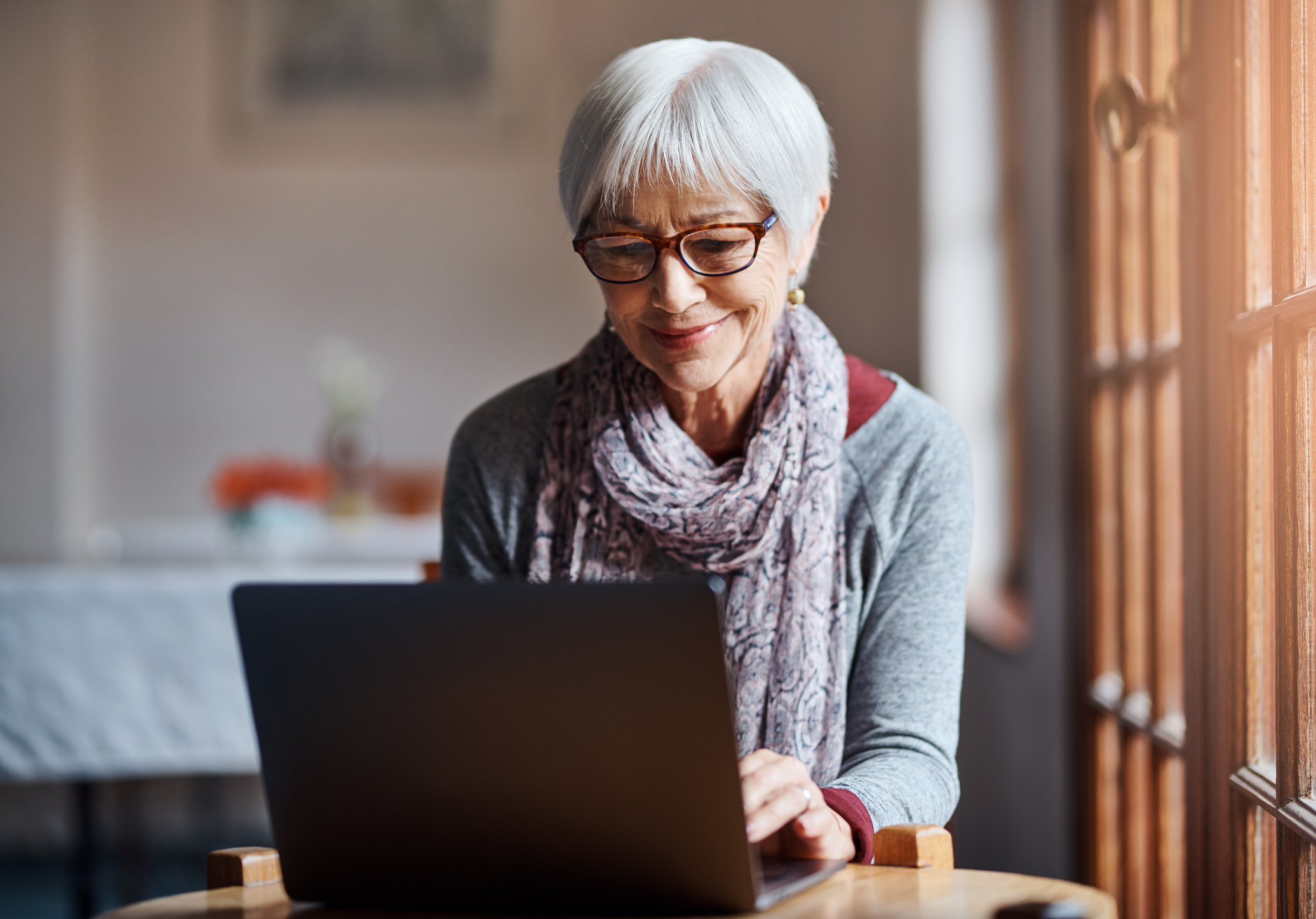 Shot of a senior woman using a laptop in a retirement home