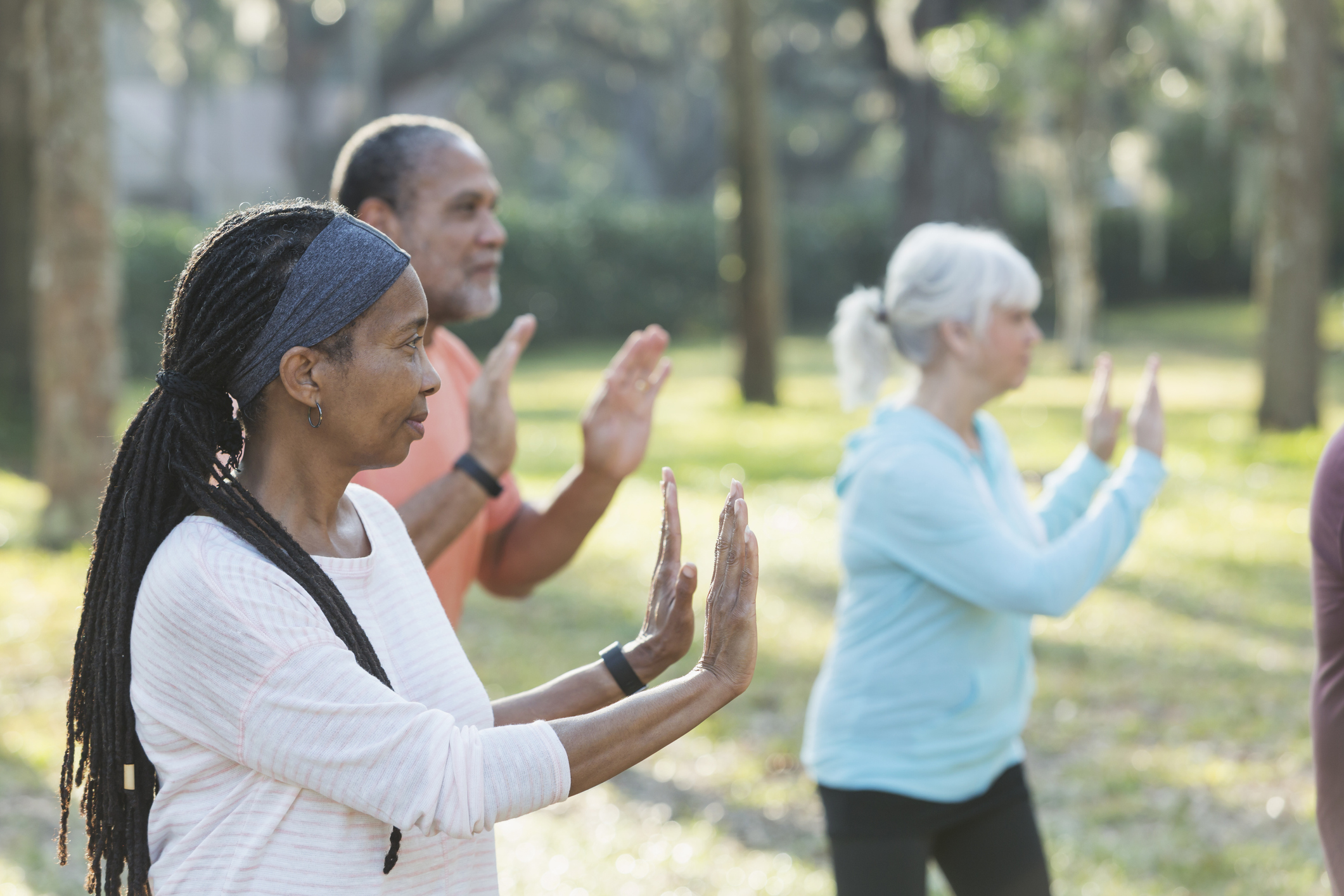 A group of three multi-ethnic seniors taking an exercise class in the park. They are practicing tai chi, standing with their hands raised. The focus is on the Africam-American woman with braided hair standing in the foreground.