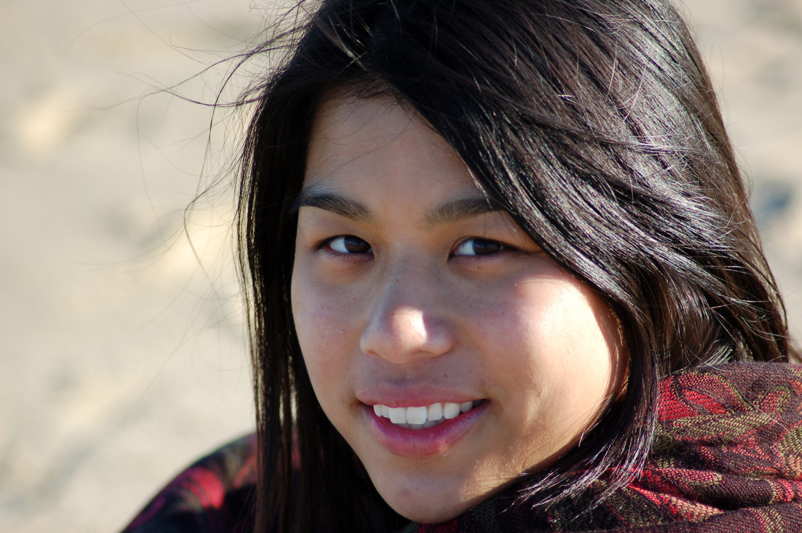 A native american woman smiles as a cold wind blows on the desert.